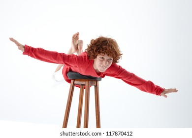 Child playing to fly with stool