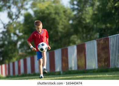 Child playing football on a green meadow