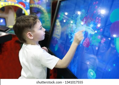 Child playing game on large touch screen in amusement park