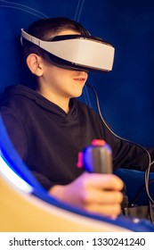 Child playing game with VR glasses. Blue illuminated cabin with joysticks. Special effects. Technology, entertainment and gaming concept with virtual reality glasses.