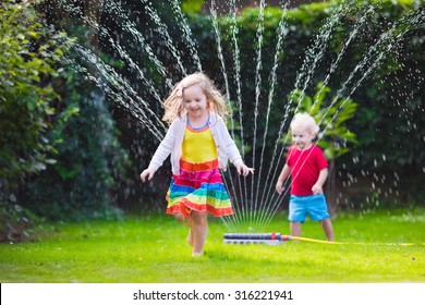 Child playing with garden sprinkler. Preschooler kid running and jumping. Summer outdoor water fun in the backyard. Children play with hose watering flowers. Kids run and splash on hot sunny day.