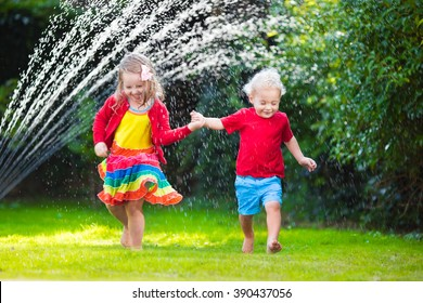 Child playing with garden sprinkler. Preschooler kid run and jump. Summer outdoor water fun in the backyard. Children play with hose watering flowers. Kids splash on sunny day. Selective focus on boy.