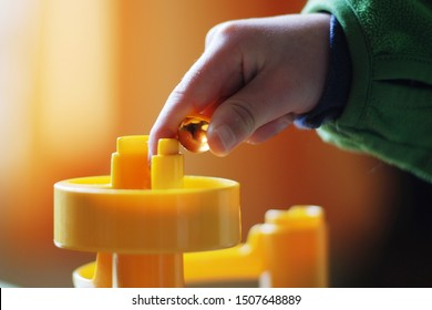 Child playing a glass marble game indoor, close up