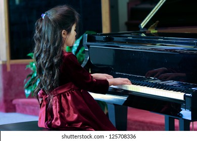Child playing grand piano in formal dress
