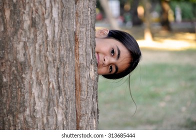 Child playing hide and seek. Cute little girl hiding behind huge tree.
