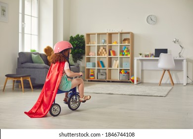 Child playing at home. Back view of a little curly girl in a red cloak and helmet rides a tricycle at home in the room. Concept of a happy childhood.
