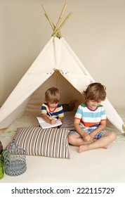 Child playing at home indoors with a teepee tent