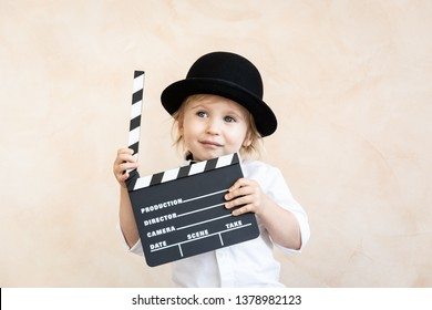 Child playing at home. Kid holding clapper board. Retro cinema concept