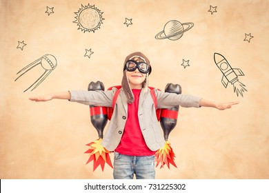 Child playing at home. Kid pretend to be astronaut. Success, creative and start up concept