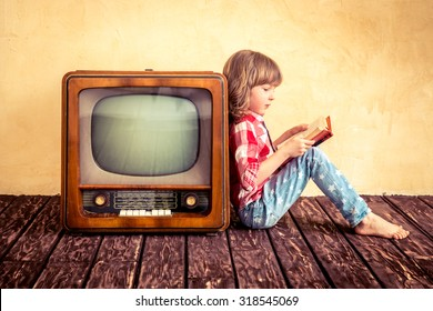 Child playing at home. Kid reading the book near retro TV. Cinema concept