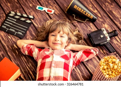 Child playing at home. Kid with vintage cinema objects. Entertainment concept. Top view