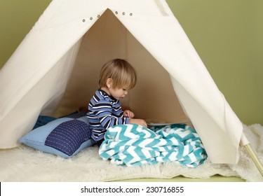 Child playing at home in a tent, drawing and art activity, showing a blank page