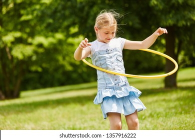 Child playing with hula hoop and training her skills