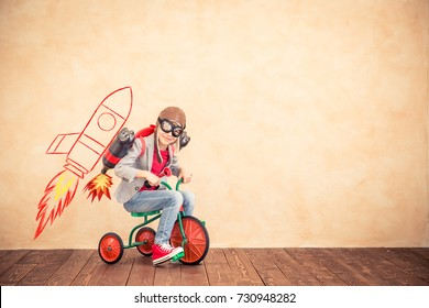 Child playing with jet pack. Kid with jetpack at home. Success, creative and startup concept