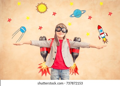 Child playing with jetpack. Kid having fun at home. Success, creative and startup concept