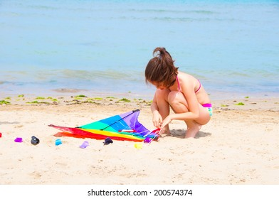 Child playing with a kite on the beach