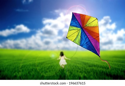 Child playing with a kite on a meadow