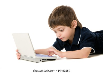 Child playing with the laptop lying on the floor