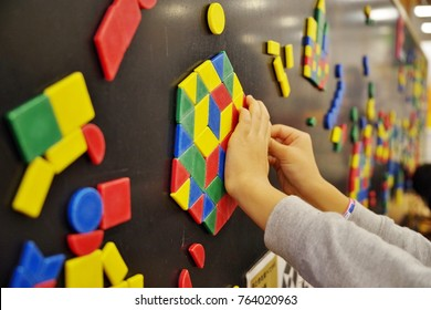Child playing magnet on blackboard