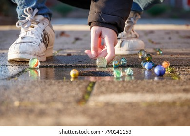 Child is playing with marbles on the sidewalk in the light of the setting sun, it is wearing cool white shoes and a black winter coat.