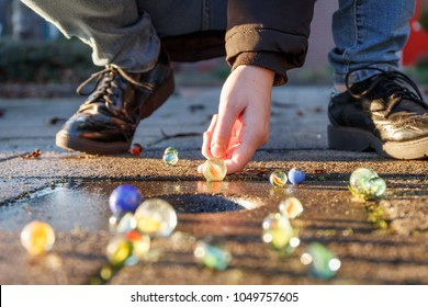 Child playing with marbles on yhe sidewalk. old-fashioned toys still in use today.