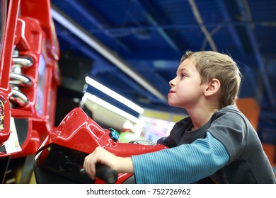 Child playing in motorcycle simulator at indoor playground