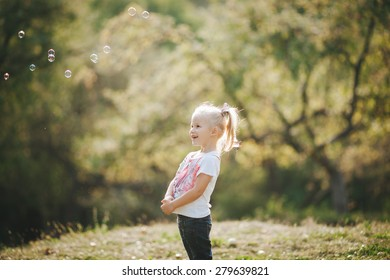 child playing in nature, playing with soap bubbles