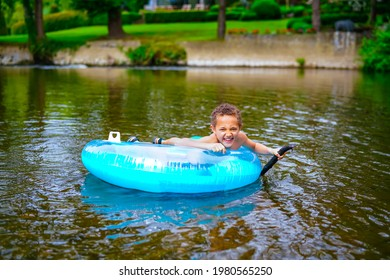 Child playing on blue inflatable buoy in wild river
