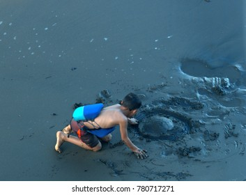 Child playing on a dark black sand beach on the Pacific coast of Panama