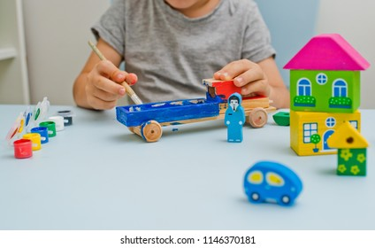 A child is playing on his desk with watercolor, drawing the wooden parts of his wooden toy. He is a young designer with many ideas. Close-up of a hand