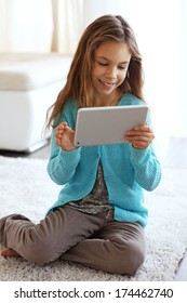 Child playing on ipad on a carpet at home