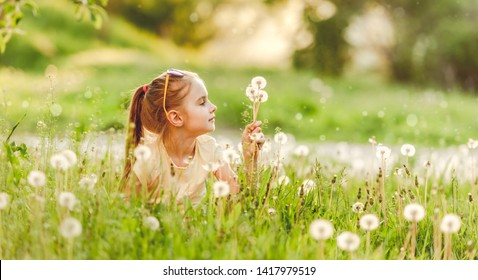 Child playing on the nature, on meadow, with flowers dandelions