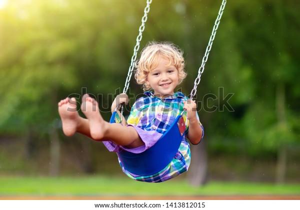 Kind, das auf einem Spielplatz im Freien spielt, bei Regen. Kinder spielen auf der Schule oder im Kindergarten. Aktives Kind auf buntem Schaukel. Gesunde Sommeraktivität für Kinder bei Regenwetter. Kleiner Junge schwingend.