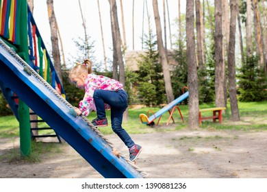 child playing on the playground on a summer day.- Image