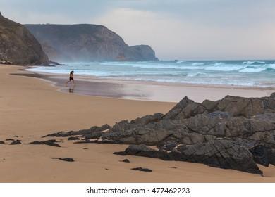 A child playing on a sandy beach. Atlantic Ocean. Portugal.