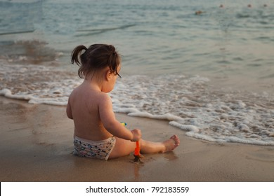 child playing on a sandy beach, sunset time, small waves