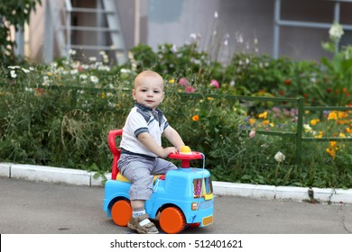 Child is playing on toy car in the park