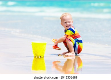 Child playing on tropical beach. Little boy digging sand at sea shore. Family summer vacation. Kids play with water and sand toys. Ocean and island fun. Travel with young children. Asia holiday.