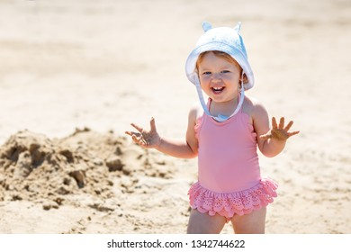 Child playing on tropical beach. Little girl digging sand at sea shore. Family summer vacation. Travel with young children