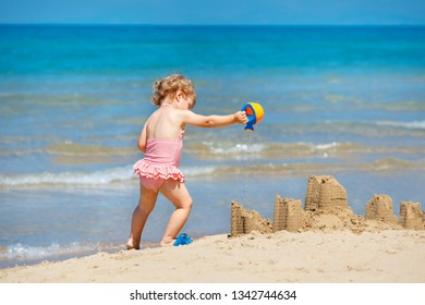 Child playing on tropical beach. Little girl digging sand at sea shore. Family summer vacation. Kids play with sand toys. Travel with young children