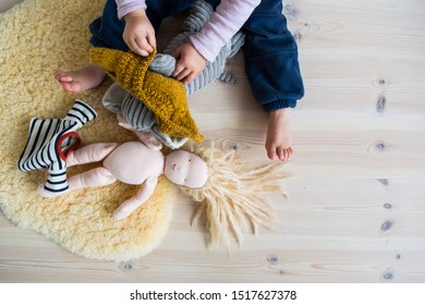 Child playing on a wooden floor with a home made Montessori doll, dressing it in selfmade clothes. On a sheep skin.