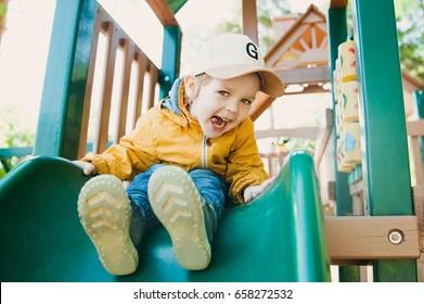 Child playing outdoors in summer. Happy kid in kindergarten. Little boy having fun on a playground outdoors in summer. Toddler on a slide.