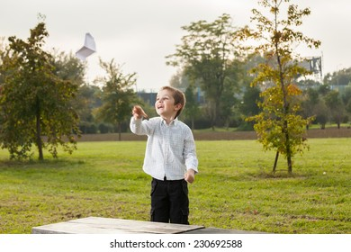 child playing with a paper airplane