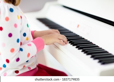 Child playing piano. Kids play music. Classical education for children. Art lesson. Little girl at white digital keyboard. Instrument for young student. Music class in school or at home.