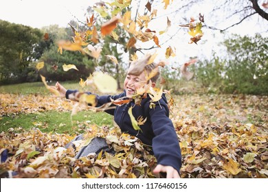 Child playing in a pile of fall leaves throwing them in the air