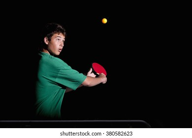 Child playing ping-pong on black background