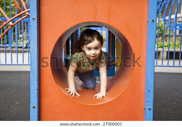 Child playing in playground tunnel
