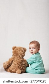 child playing with a plush toy . soft toy. funny baby with a soft toy . layout for social projects