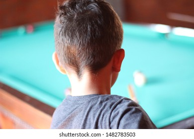 child playing at the pool table