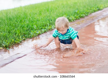 Child playing in a puddle after rain